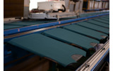 工場のレーンに並べられた生地。ここから順番にプリントされていきます。生地が引かれた台には升目があり、その升目を基準に一枚一枚ずれないように配置します。の画像