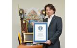 ギネス世界記録認定書を手にする執行役員・沖田氏の画像