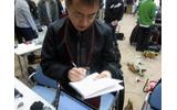 来場者から熱心にメモを取る黒川氏の画像